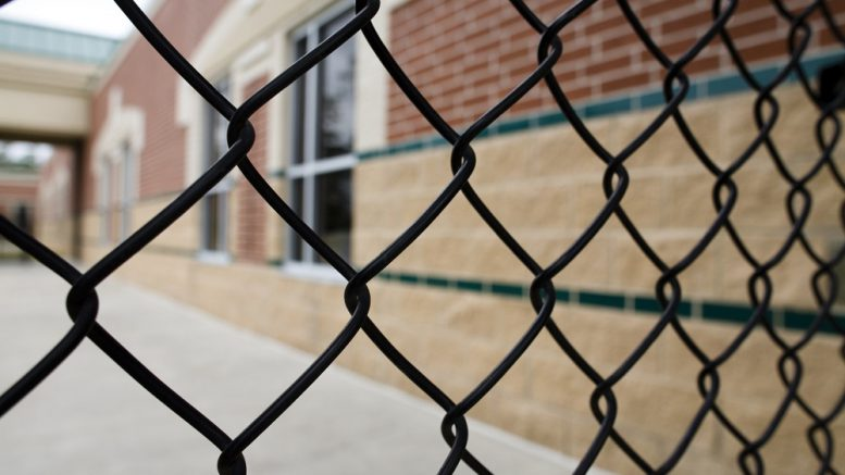 Chain link fencing alongside a brick school building.