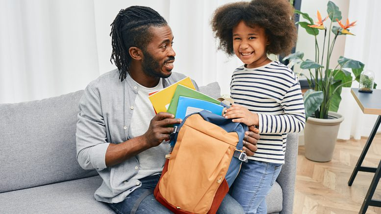Father and child pack a backpack